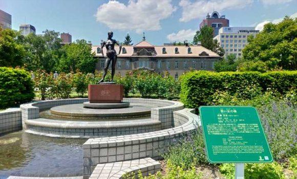 若い女の像の向こう側に見える札幌資料館